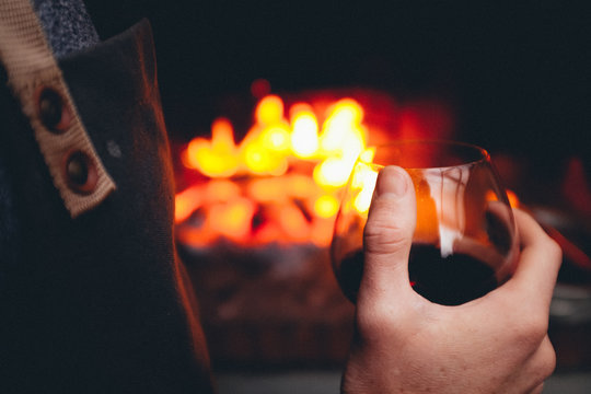 Midsection Of Person Holding Wineglasses Against Bonfire