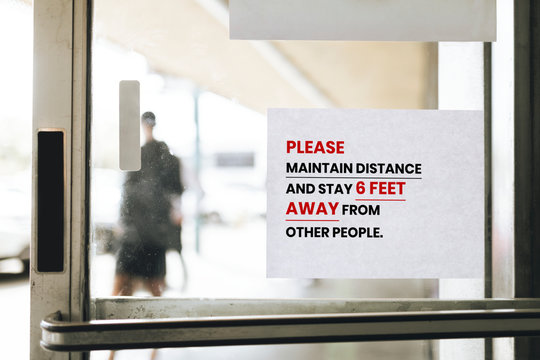 Please maintain distance and stay 6 feet away from other people paper sign on a glass door