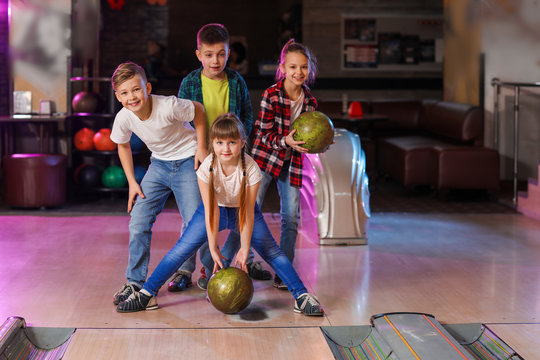 Little children playing bowling in club