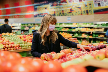 Woman in a face mask while shopping in a supermarket during coronavirus quarantine