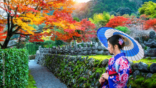 Wall mural Asian woman wearing japanese traditional kimono in autumn park.