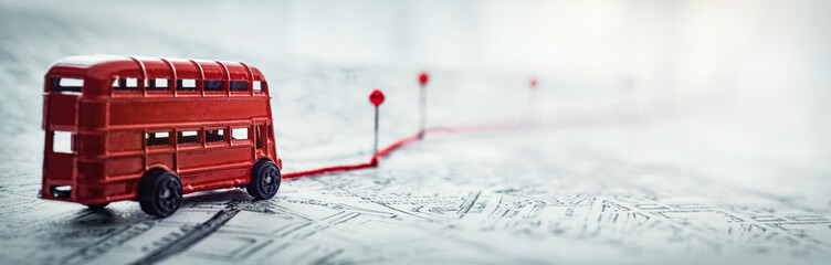 Red bus, pins and route laid on a map of the city. Concept on the  adventure, discovery, navigation, communication, logistics, geography, transport and travel topics.