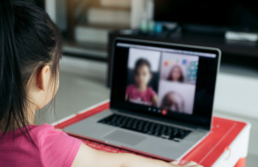 Little asian girl attending to online e-learning platform class from home while school has been...