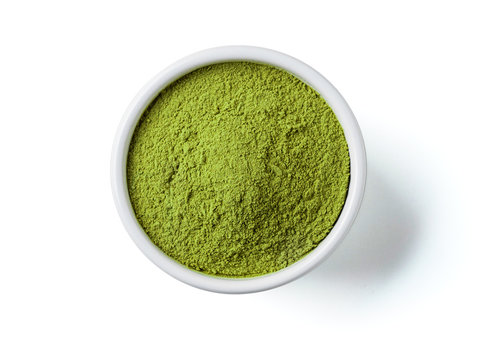 Green matcha tea powder in small white bowl on white background. Powdered maccha tea, isolated on white with clipping path. Top view or flat lay. Copy space for text or design