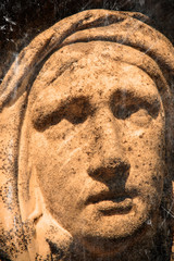 Wall Mural - Retro styled sad eyes view of Virgin Mary. Vintage stone statue of woman in grief