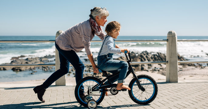 Senior woman teaching a small girl to ride a bicycle