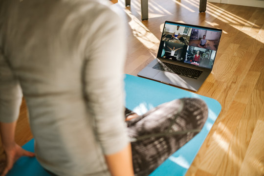 Group of people practicing yoga via video conference