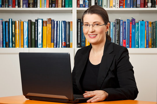 Friendly smiling woman in front of her laptop in a library, teacher, tutor, professor.