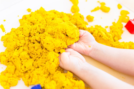 Yellow magic sand in a kids hands on a white background close up. Early sensory education. Preparing for School. Development