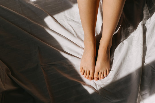 Close-up of woman feet on white bed sheet background.