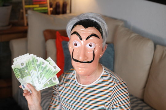 Masked person holding bunch of euros