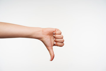 Studio photo of young attractive female's hand showing down with thumb while expressing negative emotions, isolated against white background