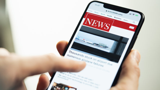 Online news on Apple iPhone. Businessman reading news about covid-19 corona on a mobile phone screen app. Newspaper and portal on internet. Displayed news are not reality related.