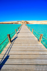 Wooden Pier at Orange Bay Beach with crystal clear azure water and white beach - paradise coastline of Giftun island, Mahmya, Hurghada, Red Sea, Egypt.