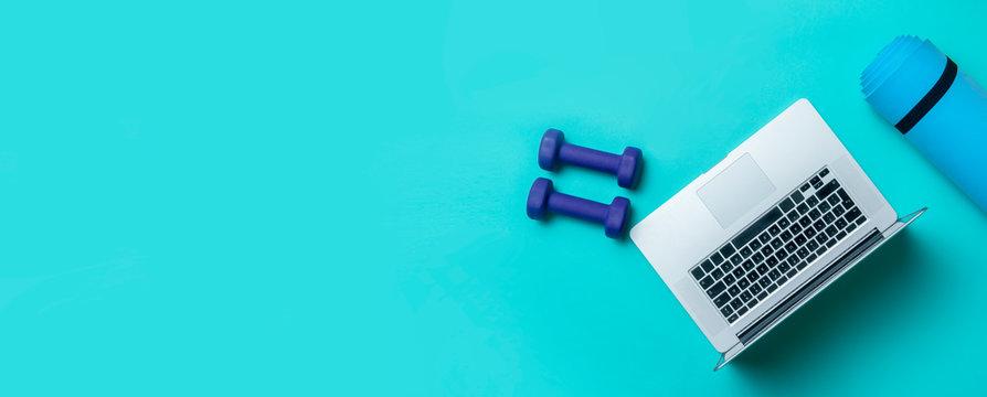 Blue dumbbells, gym mat and grey laptop on blue background. Online workout concept