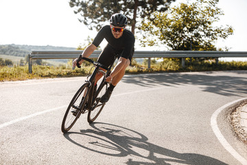 Bearded cyclist in sport clothing, protective helmet and mirrored glasses riding black bike among countryside nature during summer time. Mature man preparing for competitions and races.
