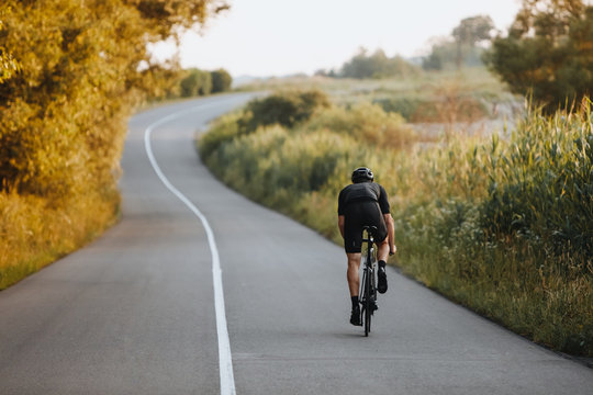 Back view of strong male cyclist with athletic body shape riding bike at the paved road among trees and green bushes in black protective helmet and sportswear. Concept of training  outdoors