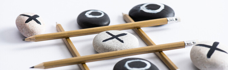 panoramic shot of tic tac toe game with grid made of pencils, and pebbles marked with naughts and crosses on white surface Wall mural