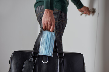 man with a suitcase and a surgical mask