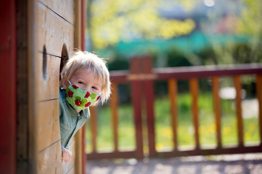 Blonde little toddler child inwearing protective mask, playing on the playground