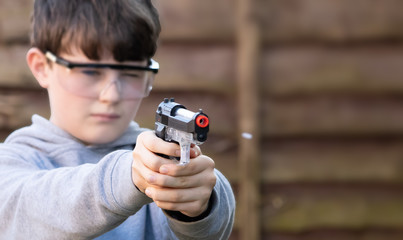 boy shoots white plastic bb pellet at target in garden with electric airsoft pistol