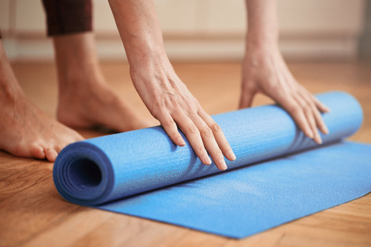 Mature woman folding blue yoga or fitness mat before or after working out at home in living room. Healthy life in covid-19 time lockdown. Focus on hand.