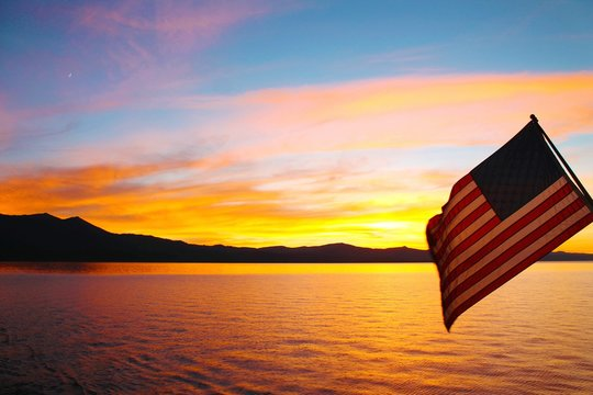 American Flag Over Lake Against Sky During Sunset