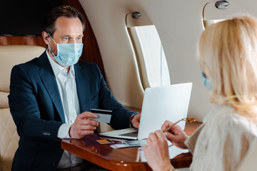 Selective focus of businessman in medical mask holding credit card and using laptop near businesswoman in airplane