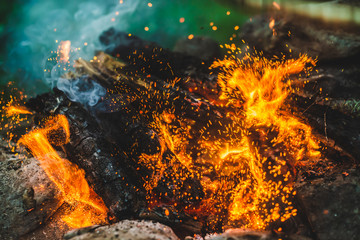 Keuken foto achterwand Brandhout textuur Vivid smoldered firewoods burned in fire close-up. Atmospheric background with orange flame of campfire and blue smoke. Warm full frame image of bonfire with glowing embers in air. Bright sparks bokeh
