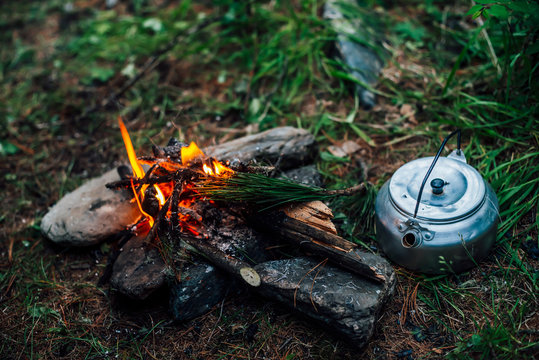 Camping kettle near small camp fire close-up. Cozy camping place in wild. Wonderful evening atmospheric background of campfire. Beautiful flame of small magic bonfire. Romantic warm place with fire.