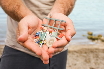 Man Holding Plastic waste from beach with the sea on the background. Close up. Sustainability and Ecologist Concept. Eco friendly Man.