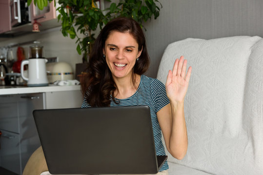 Brunette girl waves her hand, says hi and looks at her laptop making video call in her apartment. Fun greeting online. Using computer. Distance learning online education and work