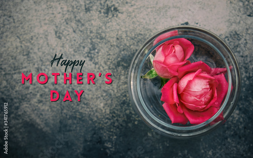 Roses floating in glass of water from top view, dark texture background with mother's day text.