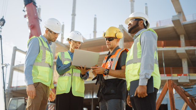 Diverse Team of Specialists Use Laptop Computer on Construction Site. Real Estate Building Project with Machinery: Civil Engineer, Investor, Businesswoman and Builder Discussing Blueprint Plan
