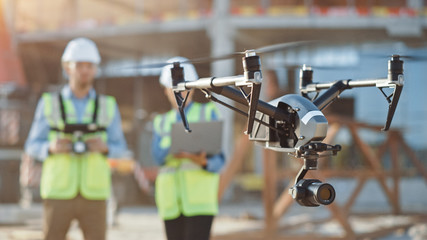 Two Specialists Use Drone on Construction Site. Architectural Engineer and Safety Engineering Inspector Fly Drone on Building Construction Site Controlling Quality. Focus on Drone