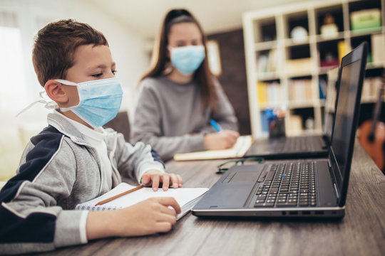 Boy and girl studies at home, wear protective masks, and doing school homework. Distance learning online education.