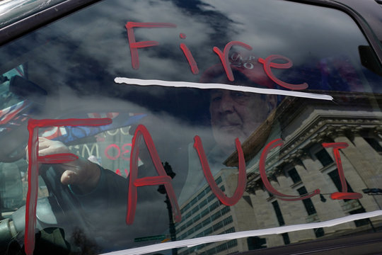 A man drives with a message written on his car's window as demonstrators take part in Operation Grid-Lock to Re-Open New York to protest against lockdown measures in the wake, during the outbreak of the coronavirus disease (COVID-19), at the New York State