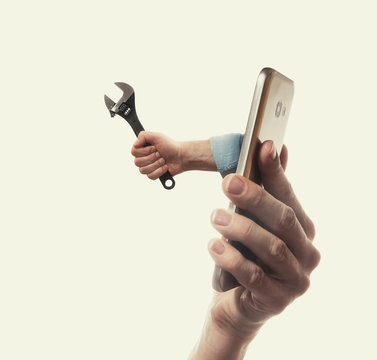 The human hand with  black wrench stick out of a smartphone screen. Concept of technical support.