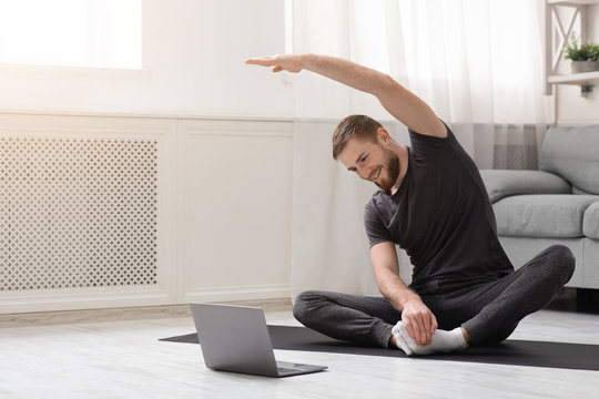 Young man practicing fitness with online training on laptop