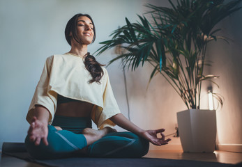 Young happy beautiful woman in cozy cropped sweatshirt and leggings practicing yoga at home sitting in lotus pose on yoga mat meditating smiling relaxed with closed eyes Mindfulness meditation concept