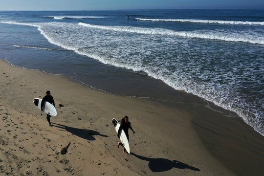 Surfers walk into the Pacific Ocean at sunrise on the 50th anniversary of Earth Day, as the global outbreak of coronavirus disease (COVID-19) continues, in Huntington Beach