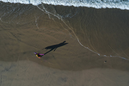 A surfer walks into the Pacific Ocean at sunrise on the 50th anniversary of Earth Day, as the global outbreak of coronavirus disease (COVID-19) continues, in Huntington Beach