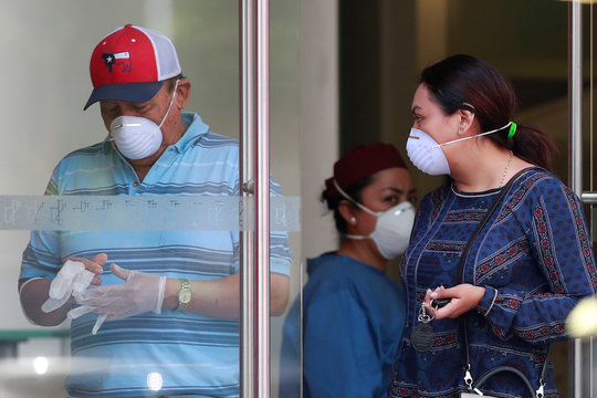 A man wearing a protective mask takes off his gloves at the entrance of a coronavirus testing site, ,as the coronavirus disease (COVID 19) continues in Mexico City