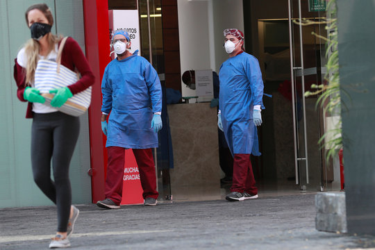 Employees in protective gear and a woman wearing a protective mask are pictured at the entrance of a coronavirus testing site, as the coronavirus disease (COVID 19) continues in Mexico City