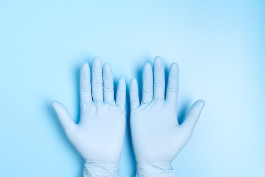 Two hands palm in medical latex hand glove isolated on blue background