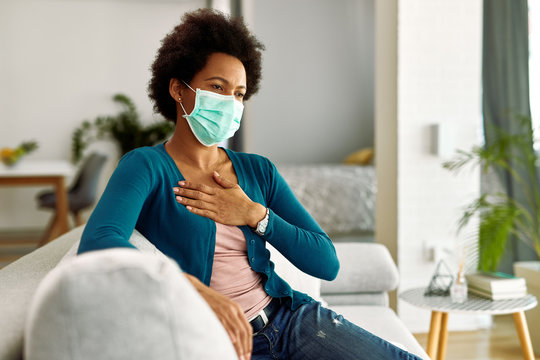 African American woman with face mask feeling chest pain while sitting at home.