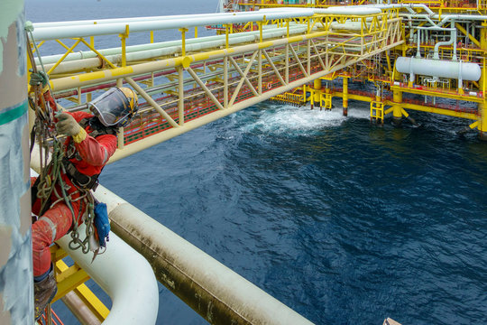 Working at height. An abseiler wearing Personal Protective Equipment (PPE) hanging  at the edge for painting with background open sea and oil and gas platform.