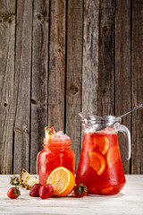Traditional beverage refreshment in a jar and glass flavored with orange, strawberry and lemon in wooden background. Picture best use for Mexican restaurant book menu concept.