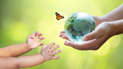 Adults are sending the world to babies. Concept day earth Save the world save environment The world is in the grass of the green bokeh background Wall mural