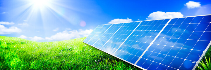 Solar Panels In Green Grass Landscape With Blue Sky And Sunlight - Clean Energy Concept